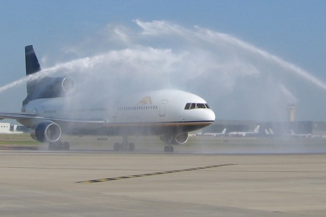 """After landing, the airplane was literally showered with """"affection"""" from the airport crash crews. The more-than-usual hoopla was because this airplane was carrying the 500,000th servicemember participating in the R&R program since it"""