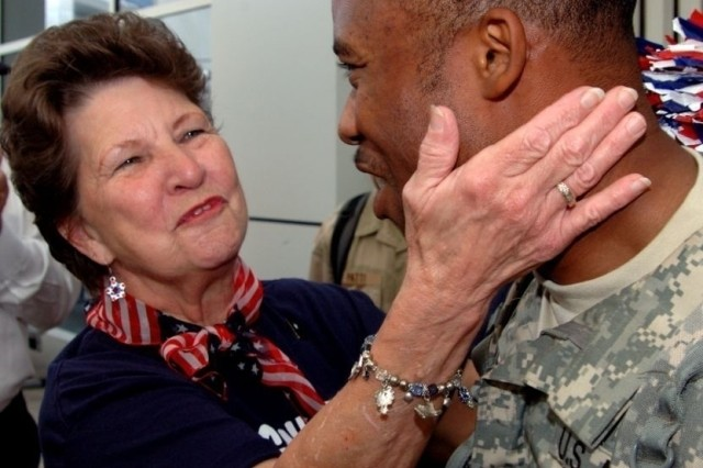 Linda Tinnerman greets a returning Soldier. She and several other greeters have welcomed hundreds of other servicemembers home on previous flights.