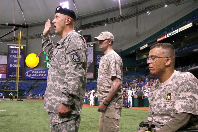 Maj. Gen. Steven Hashem, U.S. Special Operations Command, administers the oath of enlistment to Army recruits while Wounded Warriors Sgt. John Barnes (left) and Staff Sgt. Lee Jones look on at the Tampa Bay Devil Rays vs. San Diego Padres game in St. Petersburg, Fla., June 13.