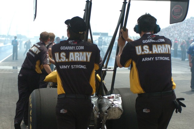 "Army Top Fuel Team members push the ""The Sarge's"" dragster into position at the 10th annual Torco Racing Fuels Route 66 NHRA Nationals in Chicago. Mr. Schumacher was unable to outrun driver Larry Dixon in the second round."