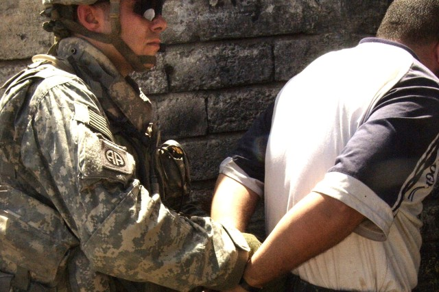 Spc. Colby Richardson detains a man after he is identified as a possible suspect.