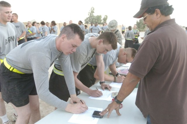Soldiers of the 3rd Heavy Brigade Combat Team, 3rd Infantry Division, sign up for the five kilometer Army Birthday Fun Run June 14, at Forward Operating Base Hammer, Iraq.