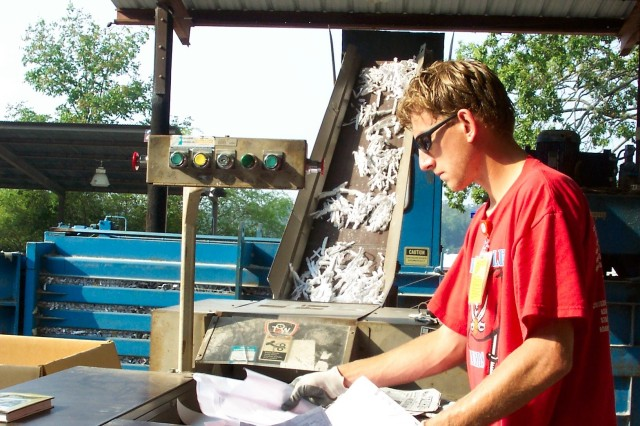 Jason Cottrill, a staff member at the recycling center here, conducts his part of the recycling process Tuesday by shredding paper, which makes its way up the conveyor belt before it is baled into squares.