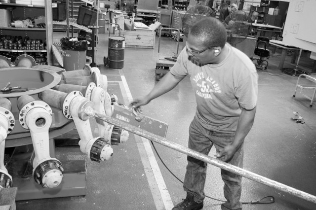 Herman Millender, heavy mobile equipment mechanic, puts road arms for the Field Artillery Ammunition Support Vehicle onto a holding fixture in the FAASV assembly line. This time-saving fixture is something new on the line in Bldg. 400. Previously, mechanics would have to take the road arms out of boxed pallets and put them on the floor until they could be used on the line.