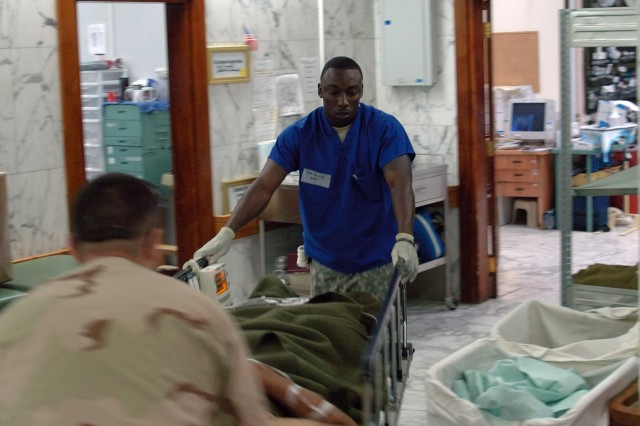 Staff Sgt. Carlington Hewitt helps rush a wounded Soldier into the trauma room at the 28th Combat Support Hospital, also known as Baghdad ER, after the Soldier's vehicle was struck by an improvised explosive device.