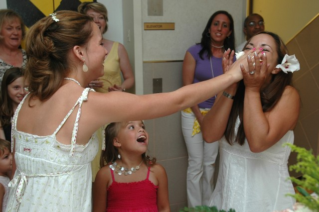 Corina Keikiaina, 13, shoves a piece of wedding cake in her mother Lilani's mouth after the wedding ceremony between Lilani and Spc. Matthew Ludwig, and intelligence analyst with the 1st Cavalry Division, June 16 at Fort Hood, Texas. Corina had to stand in for Ludwig during the cake cutting, who is currently deployed to Baghdad with the First Team. Keikiaina and Ludwig were married in a ceremony that was broadcast via video teleconference to Ludwig's location in Iraq. (U.S. Army photo by Sgt. Robert Strain, 1st Cavalry Division Public Affairs)