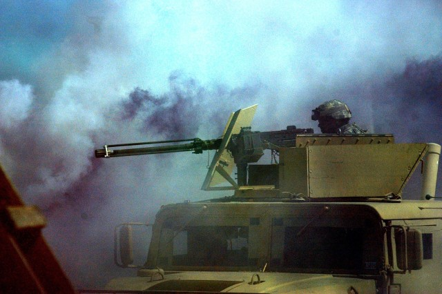 "A Soldier peers through the smoke of ""battle"" during the exercise."
