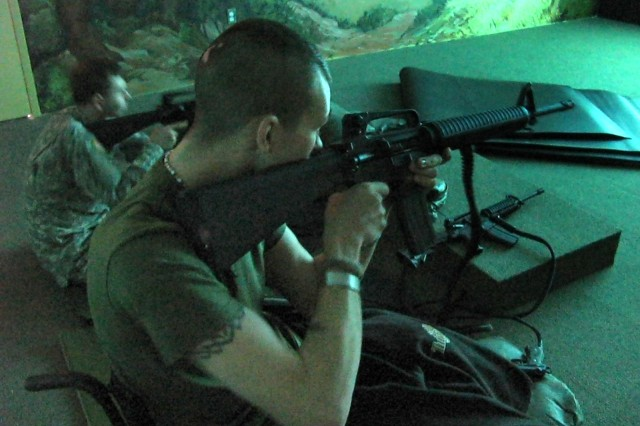 Marine Lance Cpl. Eric Frazier, a reservist from Nashville Tenn., fires an M-16 rifle electronically tied into the Fire Arms Training System at Walter Reed Army Medical Center. A computer system runs scenarios, and servicemembers fire a variety of electronically integrated weapons at a large screen. Frazier was an expert shooter prior to joining the military and is thankful he could return to the sport after his injuries.