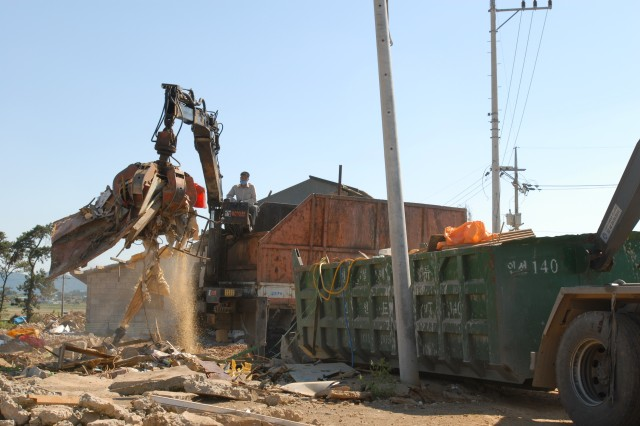 A contractor uses heavy equipment to haul away debris from a building site on Camp Humphreys, South Korea, to prepare the land for construction.