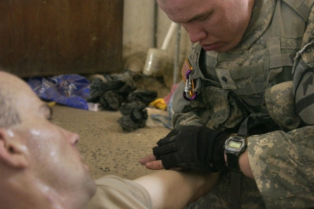 Spc. James Choclin provides first aid to Pvt. Joshua Johnson.