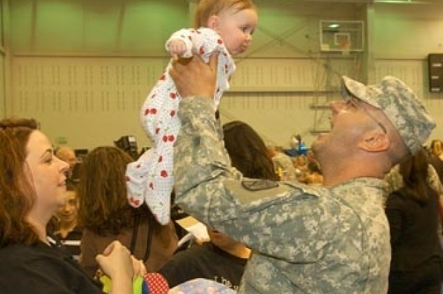 Sgt. Michael Taylor holds up his 5-month-old daughter, Emily, June 15, while his wife, Amber (left), watches. Taylor hadn't seen his daughter since she was 2 weeks old.