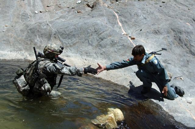 An Afghanistan policeman assists 2nd Lt. Jonathon Reabe.