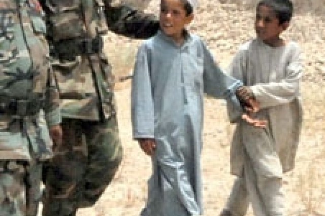 A young Afghan boy to a guard at a governor's compound. The Taliban had fitted the naAfA-ve boy with explosives and had given him instructions on how to detonate it, but he'd forgotten what to do.