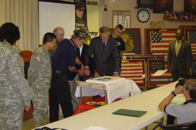 Members of the Topeka Chapter of the Association of the United States Army (AUSA), Topeka Mayor Bill Bunten, MG (Ret) Gene Krase, and American Legion Post #1 Commander Jack Valliere participate in the Birthday cutting celebration in honor of the Army's 232nd Birthday Celebration in Topeka, KS .