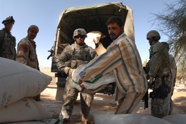 Sgt. Richard Elerick and an Iraqi man unload humanitarian relief supplies for the villagers.