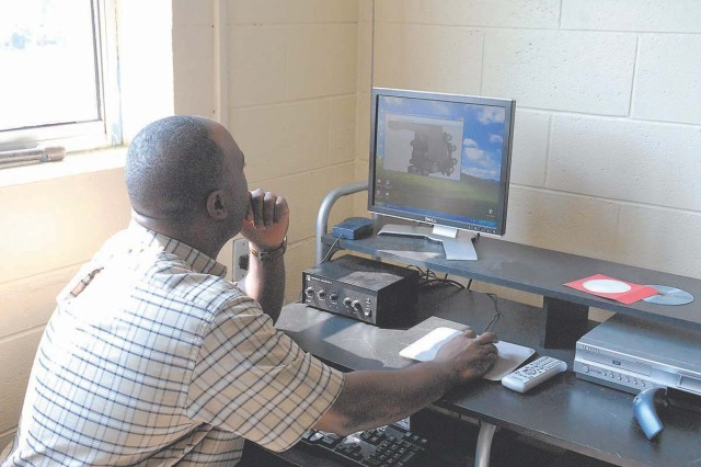 Charles Taylor, Wheel Vehicle Mechanic School instructor, demonstrates how he controls the new NGRAIN technology, a 3-D animation software that allows students to receive virtual hands-on training before practicing on real vehicles.