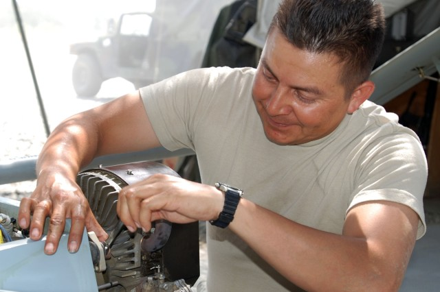 "Army Staff Sgt. Pablo Villanueva, Bravo Company, 173rd Special Troops Battalion (Airborne) takes an engine off a RQ-7 Shadow 200 Unmanned Aerial Vehicle on Forward Operating Base Fenty in Jalalabad, Afghanistan, June 19, while conducting ""preventive maintenance daily."""