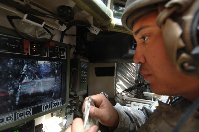 "Spc. Ruben Casiano Jr. uses his Stryker vehicle's remote weapon system to scan the area for ""enemy"" contact."
