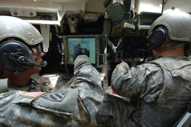 """Staff Sgt. George Adams (left) and Spc. Brenton Steckel monitor the Force XXI Battle Command Brigade-and-Below and Remote Weapons System screens in their Stryker vehicle, while looking for """"enemy contacts."""""""