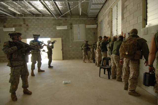 Soldiers guard captured role-playing insurgents.