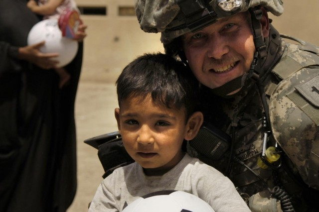 Sgt. 1st Class Jeffrey Whitworth gives a child a soccer ball in Al Furat, Iraq. Sgt. 1st Class Whitworth is assigned to the National Police Transition Team.