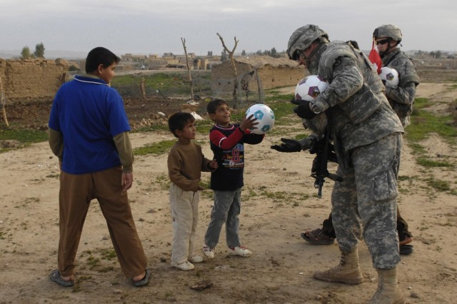 Lt. Col. Drew Meyerowich and fellow Soldiers pass out soccer balls to Iraqi children in the Hawijah district of Kirkuk province. The Soldiers are from the 25th Infantry Division.