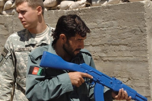 Spc. Jeremiah Nemeth teaches tactics to an Afghan policeman at Forward Operating Base Kalagush.