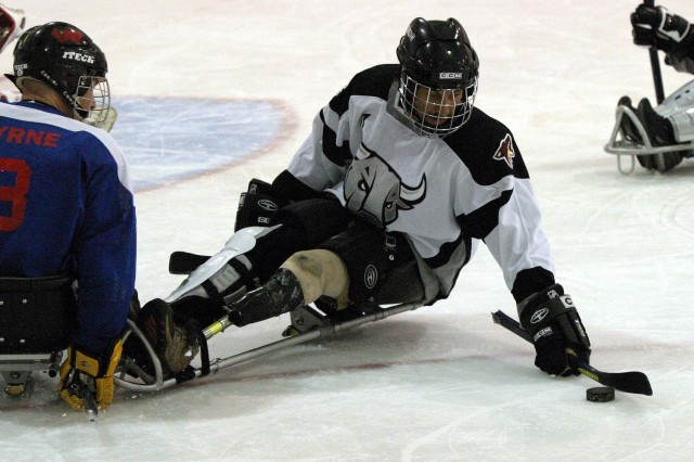 """(Left) Mike Marsh, player for the San Antonio Rampage Sled Hockey Team, reaches for the puck during a June 16 game vs. the San Antonio Men of War, which is normally a """"stand-up"""" team. The Rampage team, comprising wounded warriors and civilians, won the game 3-1."""