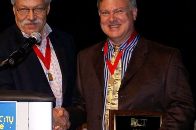 Jon Kerkhoff, left, American Association of Community Theatre, congratulates Jim Sohre for being named a Fellow of the organization.