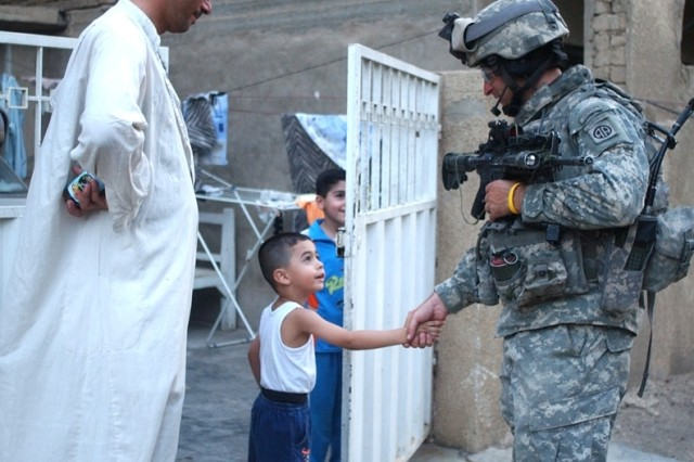 A Soldier interacts with children.