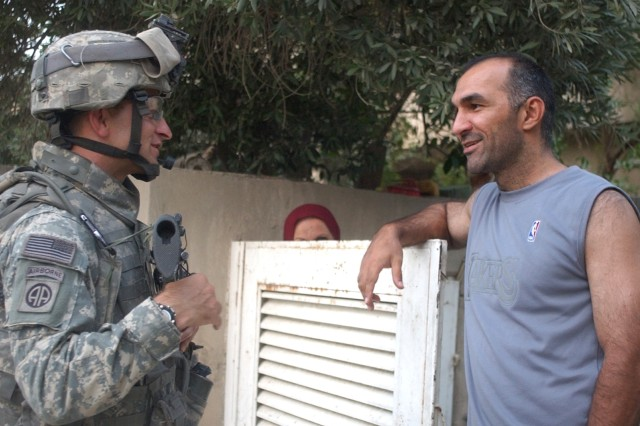 Sgt. 1st Class Rob Farnsworth chats with a resident.