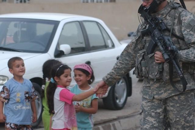 2nd Lt. Evan Wolf, the platoon leader, greets children.
