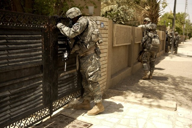 Soldiers look into the courtyard of an abandoned house before entering it.