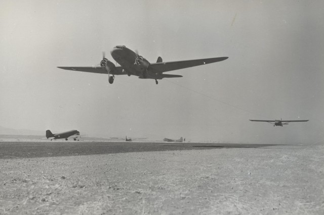 The Douglas C-47 of the Troop Carrier Command was the workhorse of the airborne forces and was used to transport paratroopers or to tow glider borne troops.   This image shows a C-47 with glider in tow training at Oujda, French Morocco, North Africa, on 17 June 1943, less than a month before the Sicily invasion.  (World War II Signal Corps Collection).