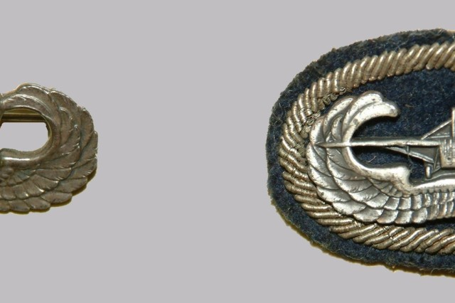 The Army Parachutist Badge (left) was designed by Captain William P.  Yarborough, 501st Parachute Infantry Battalion, and approved on 10 March 1941.  There were concerns that the badge was too small, so Yarborough designed an oval cloth background trimming.  The Glider Badge (right with a background trimming) was adopted on 2 June 1944, only a few days before the D-Day assault.