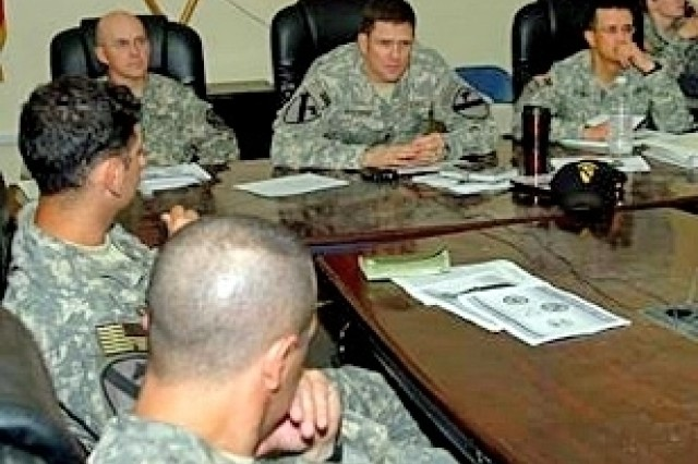 """Col. Mike Bridges (upper left), Lt. Col. Peter Andrysiak (center), and Maj. Steve Espinoza (right), along with other members of the 1st """"Ironhorse"""" Brigade Combat Team, 1st Cavalry Division, listen intently to advice from Austin, Texas, City Manager Toby Hammett Futrell about Austin's local government model, during a conference call at Camp Taji, Iraq, June 28."""