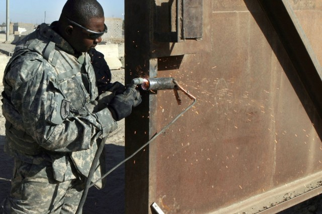 Sgt. Okhumheode Mazone, from the 3rd Infantry Division, attached to the II Marine Expeditionary Force, repairs the gateway to Combat Observation Post Steel in Ar Ramadi, Iraq.