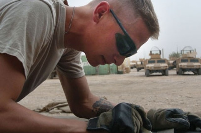 Pvt. Robert Sauer, from the 3rd Infantry Division, measures a sheet of steel that will be attached to a vehicle for armor protection.