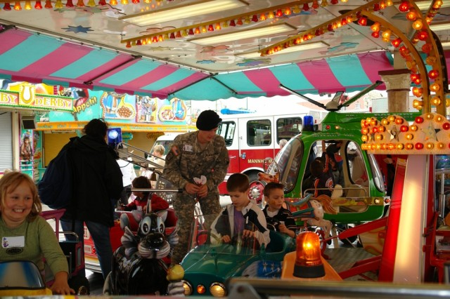 "MANNHEIM, Germany - Spc. Jon Kruskamp, 72nd Signal Battalion, ensures his little buddies are set for a merry-go-around plane ride at the German-American summer fest here. Traditionally, one morning of the annual fest is dedicated to children from nearby German and U.S. military communities. More than 180 kids participated in this year's ""Day Just for Kids"", which has been held for 23 years and is co-organized by U.S. Army Garrison Mannheim's Army Community Service and the German carnival association."