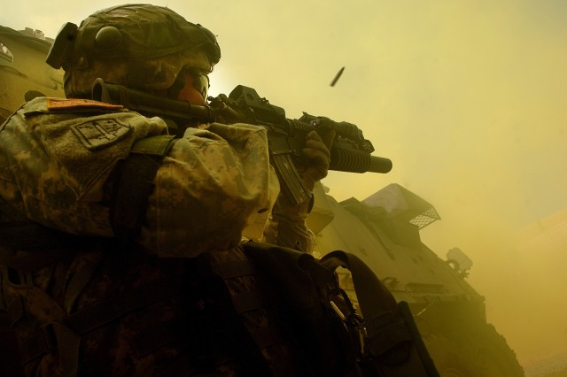 A Soldier fires on role-playing insurgents.