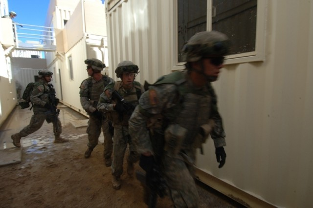 Soldiers clear buildings of role-playing insurgents.