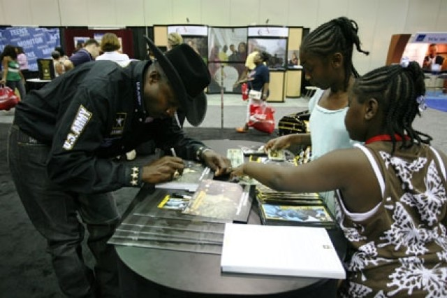 Fred Whitfield Army sponsored World Champion Roper, at the NAACP Convention signing autographs for young fans visiting the Army exhibit booth.