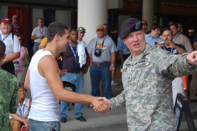 SGT. Scott Dickson, Harmony in Motion, congratulates a winning contestant directing him to receive his prize from local recruiters at the Army tent.