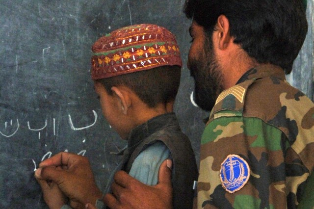 An Afghan Soldier helps to teach during handwriting class.