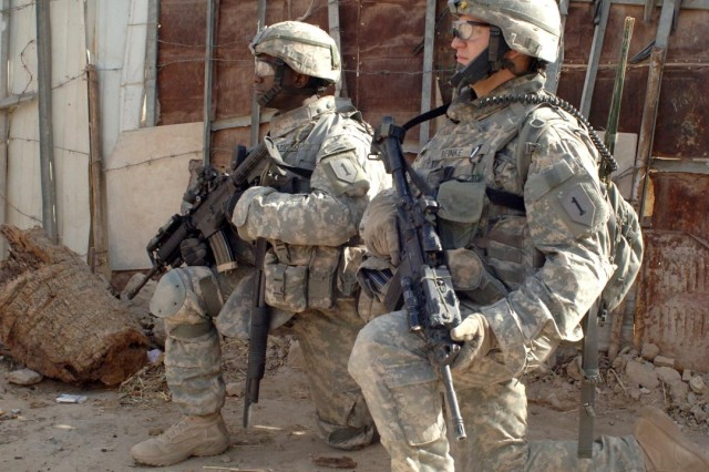 Pfc. Andrew Reinke (right) and Capt. Jermaine Hampton provide security for fellow Soldiers during the operation.