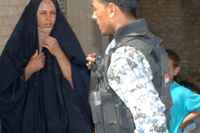Iraqi policeman speaks to a resident.