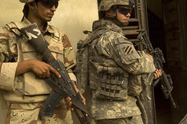 A Soldier from the 3rd Infantry Division and an Iraqi Soldier prepare to clear a building in Arab Jabour, June 25.
