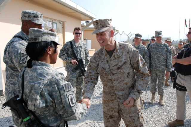 Gen. Peter Pace, chairman of the Joint Chiefs of Staff greets Master Sgt. Karen Beckford, 173rd Brigade Support Battalion (Airborne) July 19 with a coin at Forward Operating Base Fenty, Afghanistan.