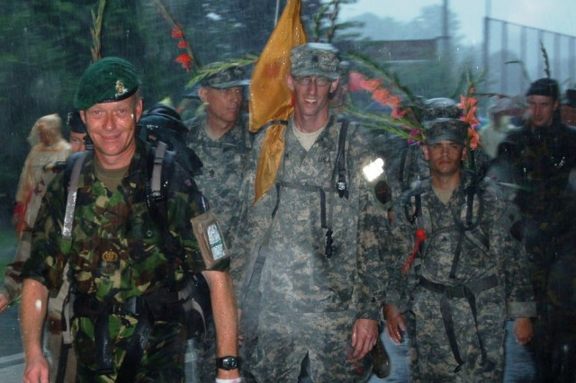 NIJMEGEN, the Netherlands - As rain poured down here July 20, United Kingdom army Warrant Officer John Hayes (left), from NATO's Joint Forces Command in Brunssum, the Netherlands; Command Sgt. Maj. Ralph Rusch, U.S. Army Garrison Schinnen, the Netherlands; Sgt. Steven La Plume, USAG Brussels, Belgium; and Sgt. José Burgos, USAG Benelux, Belgium, complete the Nijmegen Four Day March.  Each day of the march covered 40 to 50 kilometers (roughly 25 to 30 miles), with more than 36,000 people from 63 nations - including 4,500 servicemembers - participating. (Photo by Tom Budzyna)
