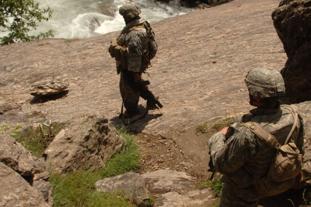 Soldiers descend the rugged terrain.